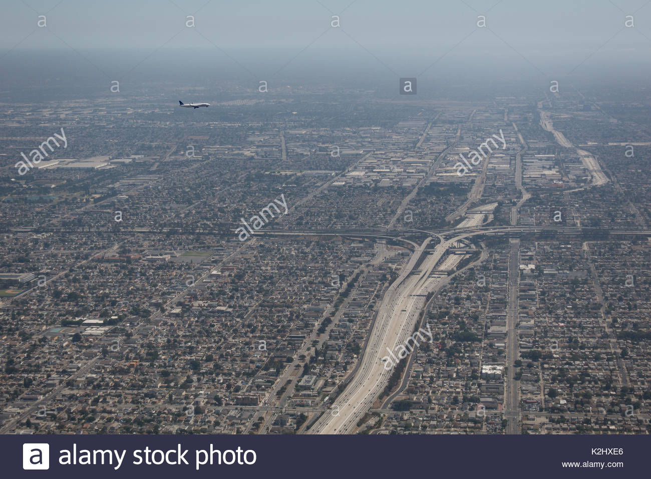 A commercial airplane is on approach to LAX (Los Angeles International Airport) over Interstate 5 highway in California. - Stock Image