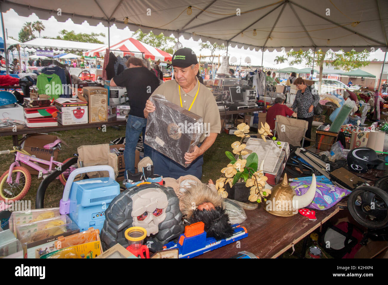 A Hispanic proprietor organizes  an amusement park rummage sale in Costa Mesa, CA. Note variety of objects offered for sale. - Stock Image