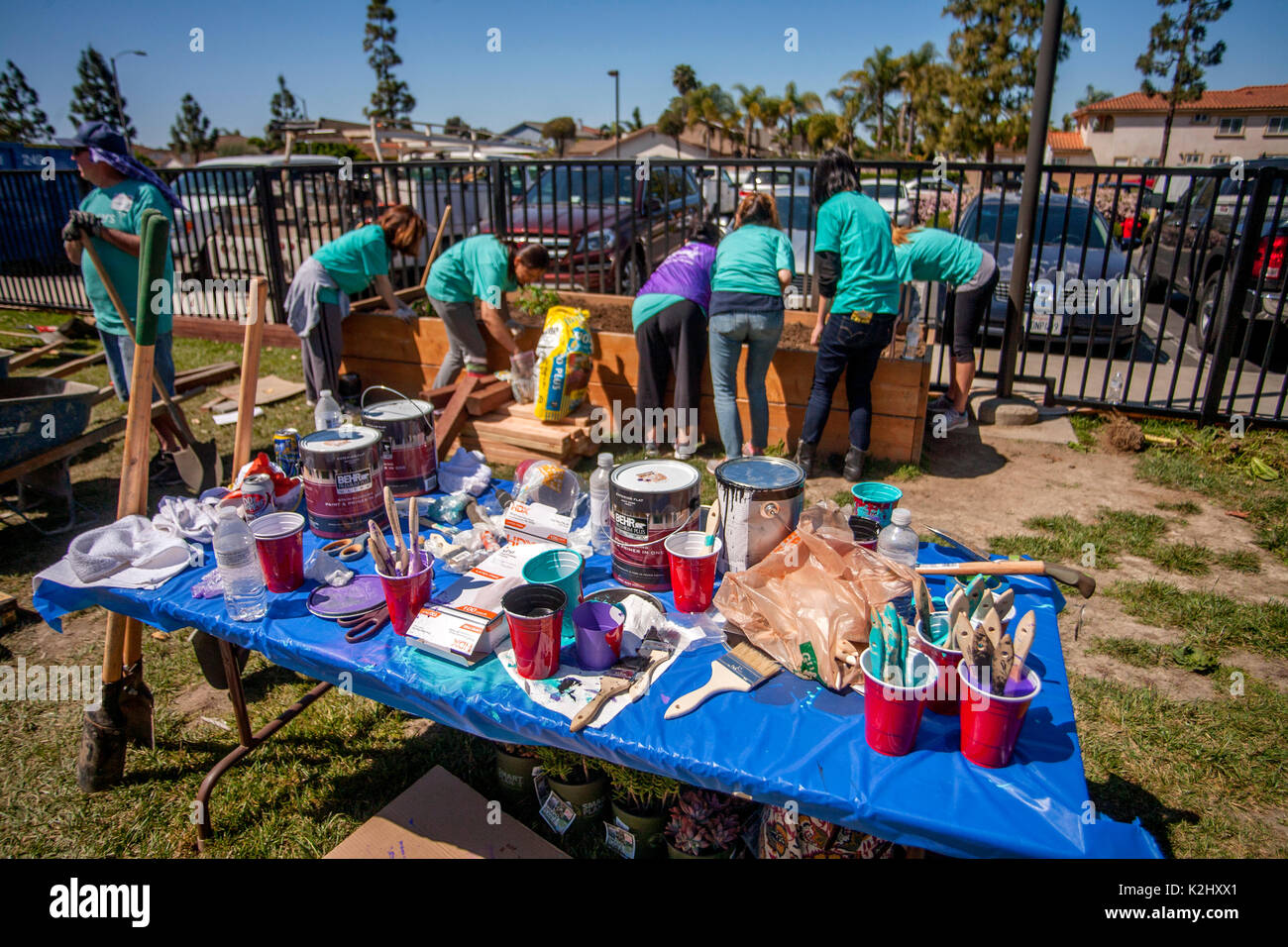 Multiracial local volunteers work together at an outdoor planter boxconstructing a new playground in fountain valley ca note table full of paint and