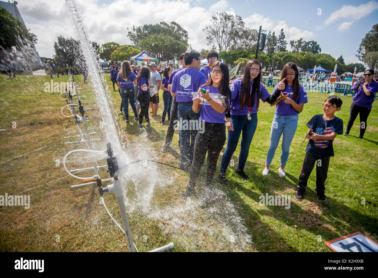 Asian American instructors help an enthusiastic boy, right, launch a water rocket with a blast of compressed air in Huntington Beach, CA. Made out of a plastic soda bottle, a water rocket uses water as its reaction mass. The water is forced out by compressed air. It operates on the principle of Newton's third law of motion. Note safety glasses. - Stock Image
