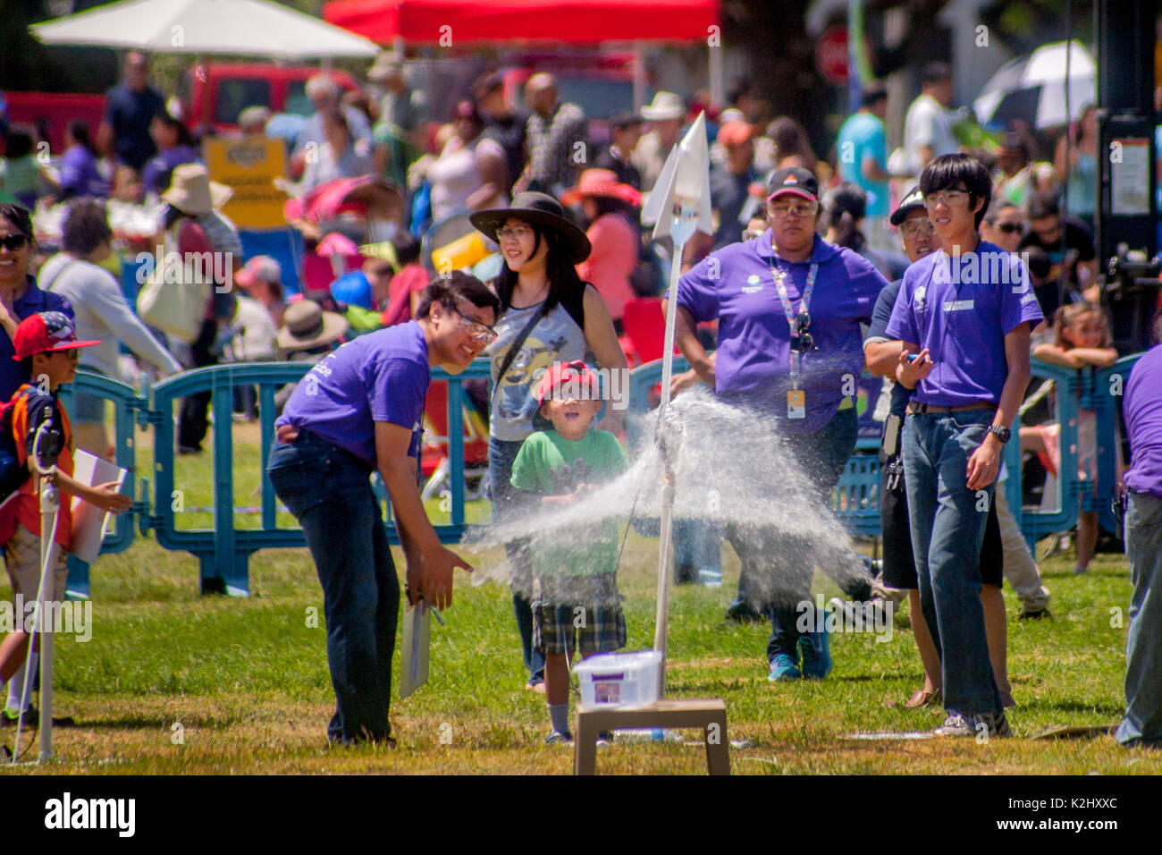 Asian American and Hispanic instructors help an enthusiastic boy launch a water rocket with a blast of compressed air in Huntington Beach, CA. Made out of a plastic soda bottle, a water rocket uses water as its reaction mass. The water is forced out by compressed air. It operates on the principle of Newton's third law of motion. Note safety glasses. - Stock Image