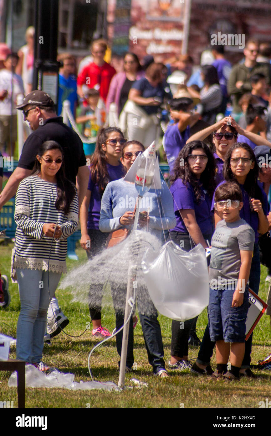 Asian American and Hispanic instructors help an enthusiastic boy launch a parachute-equipped water rocket with a blast of compressed air in Huntington Beach, CA. Made out of a plastic soda bottle, a water rocket uses water as its reaction mass. The water is forced out by compressed air. It operates on the principle of Newton's third law of motion. Note safety glasses. - Stock Image