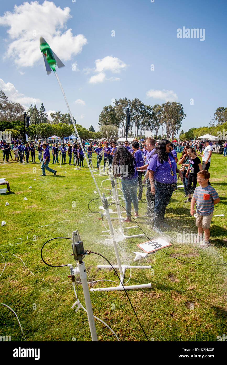 Asian American instructors help an enthusiastic boy launch a parachute-equipped water rocket with a blast of compressed air in Huntington Beach, CA. Made out of a plastic soda bottle, a water rocket uses water as its reaction mass. The water is forced out by compressed air. It operates on the principle of Newton's third law of motion. Note safety glasses. - Stock Image