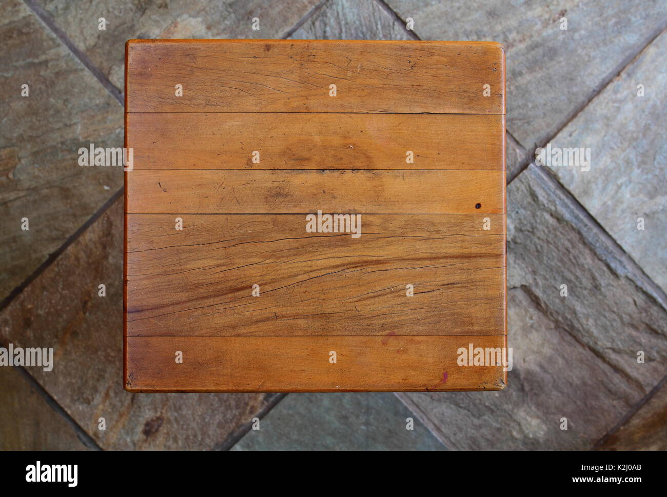 A weather-beaten and worn yellow wood table top viewed from directly above with copy space and a clear background - Stock Image