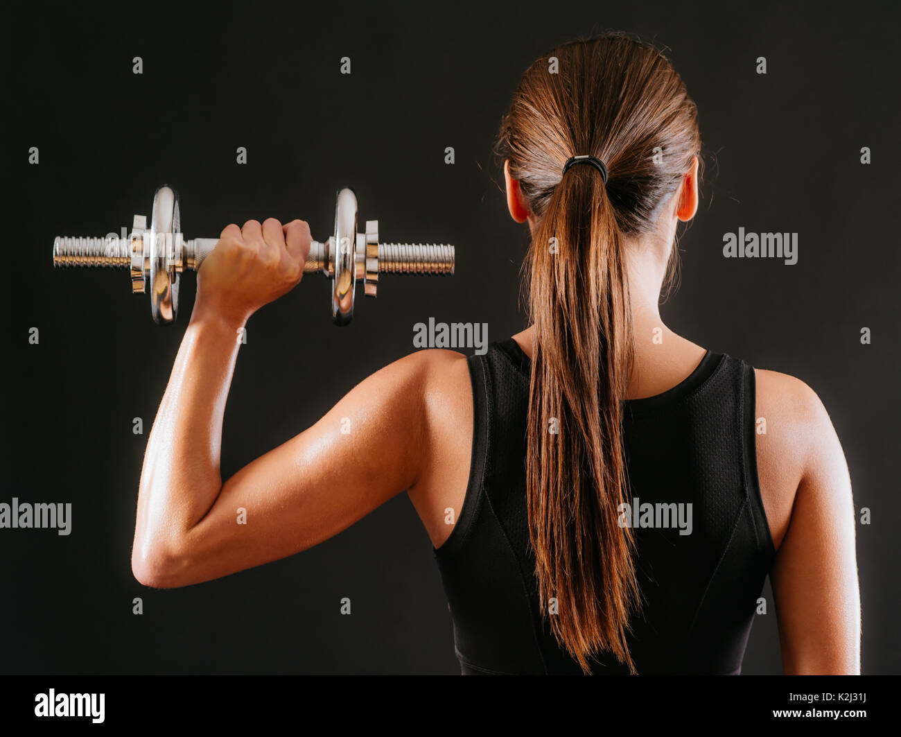 Photo of the back of a young woman doing a shoulder press with a dumbbell over a dark background. - Stock Image