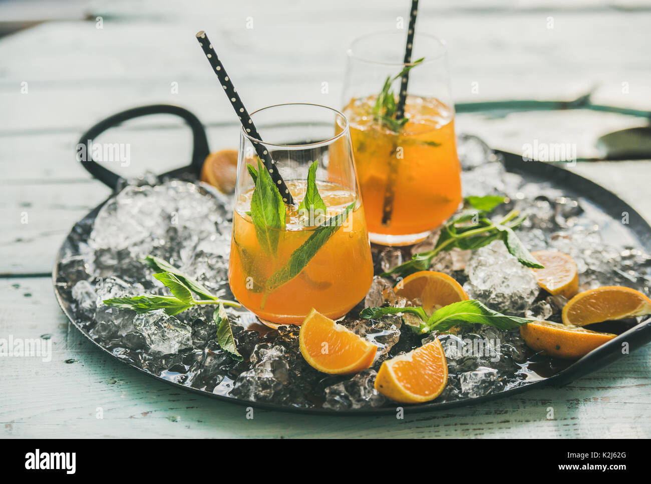 Refreshing cold alcoholic summer citrus cocktail with orange, peppermint and ice in stemless glasses on tray over light blue wooden table background,  - Stock Image