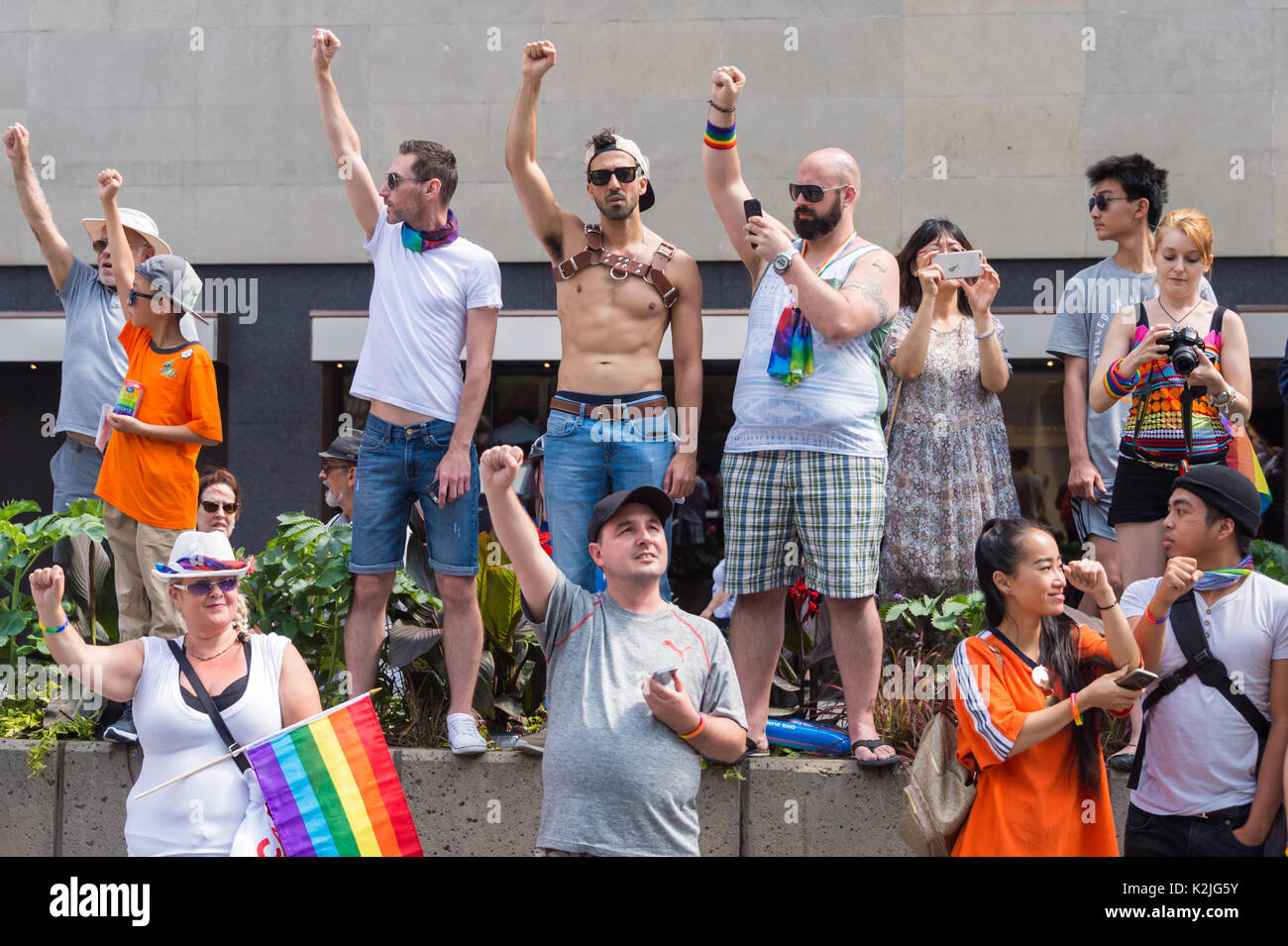 Montreal, CANADA - 20 August 2017: Spectators raise their fists during moment of silence at Montreal Gay Pride parade. - Stock Image