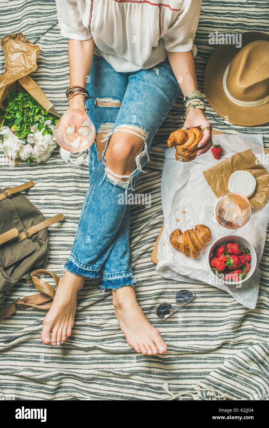 French style romantic picnic setting. Woman in denim pants sits with glass of rose wine, strawberries, croissants, brie cheese, hat, sunglasses, peony - Stock Image