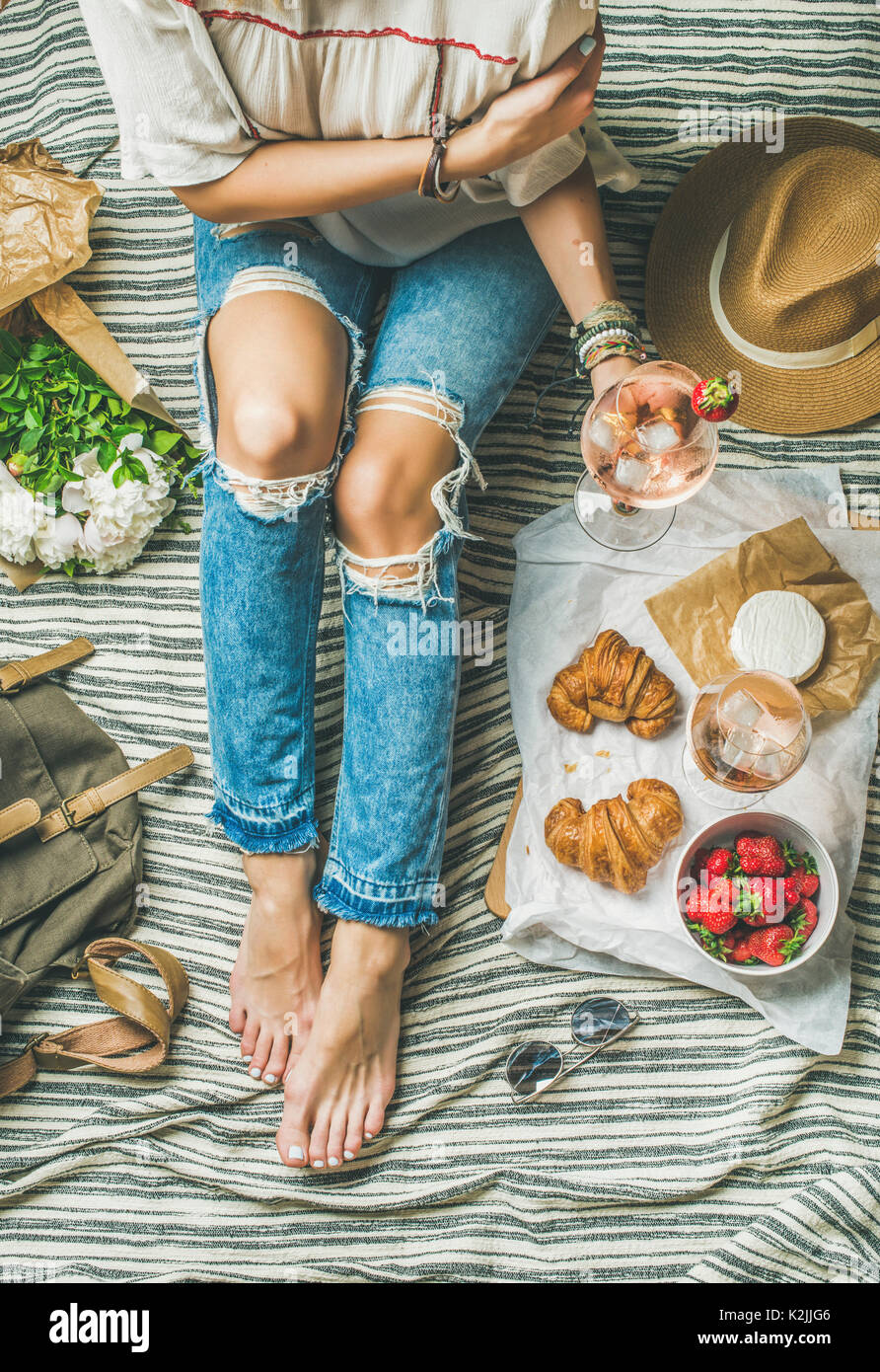 French style romantic picnic setting. Woman in denim pants sits with glass of ice rose wine, strawberries, croissants, brie cheese, hat, sunglasses, p - Stock Image
