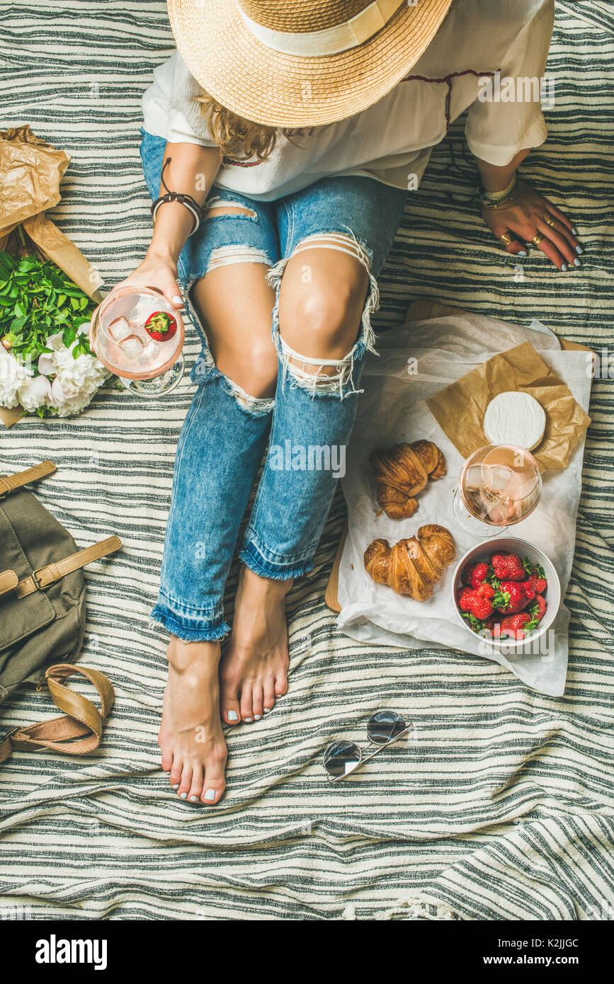 French style romantic picnic setting. Young woman in denim pants with glass of ice rose wine, strawberries, croissants, brie cheese, hat, sunglasses,  - Stock Image