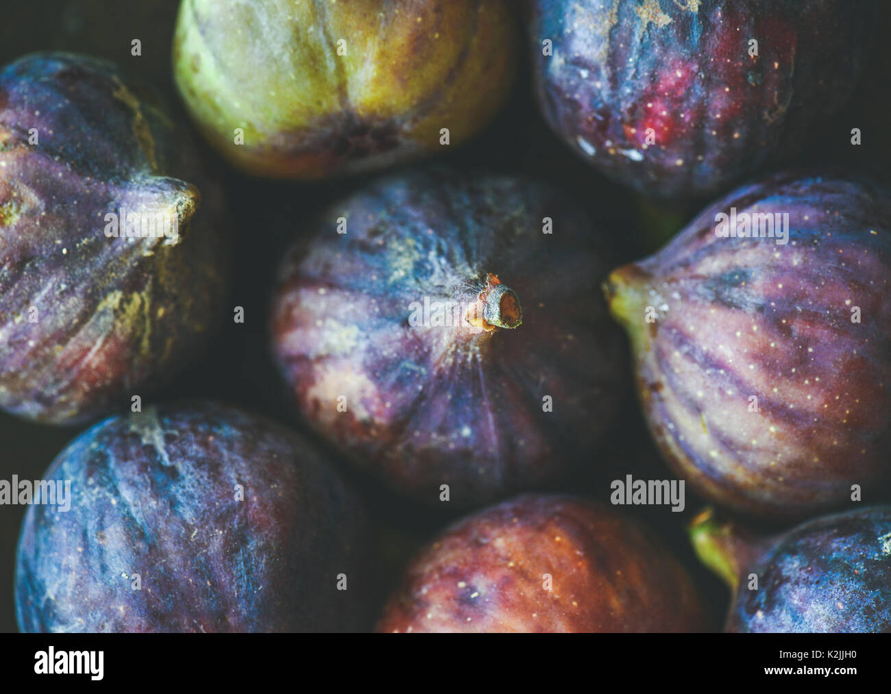 Close-up of fresh ripe purple figs, top view. Food texture and background. Organic fruit, local produce, farming, healthy food concepts - Stock Image