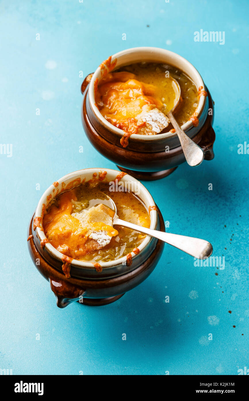 Authentic French Onion soup with dried bread and cheddar cheese in bowl on blue background - Stock Image