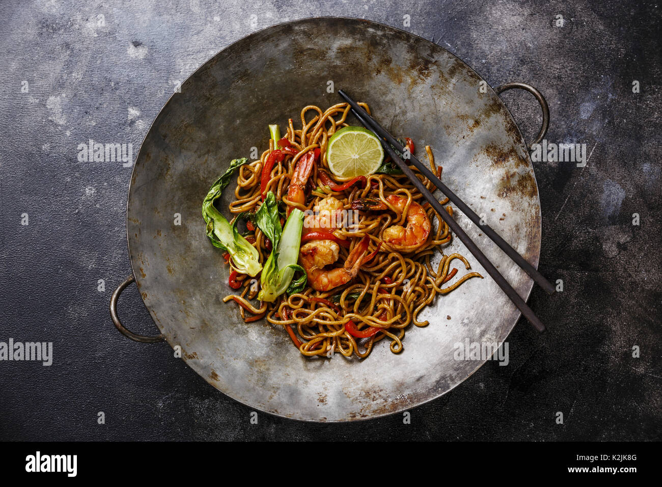Udon noodles stir-fried with Tiger shrimps and vegetable in wok cooking pan on dark background Stock Photo
