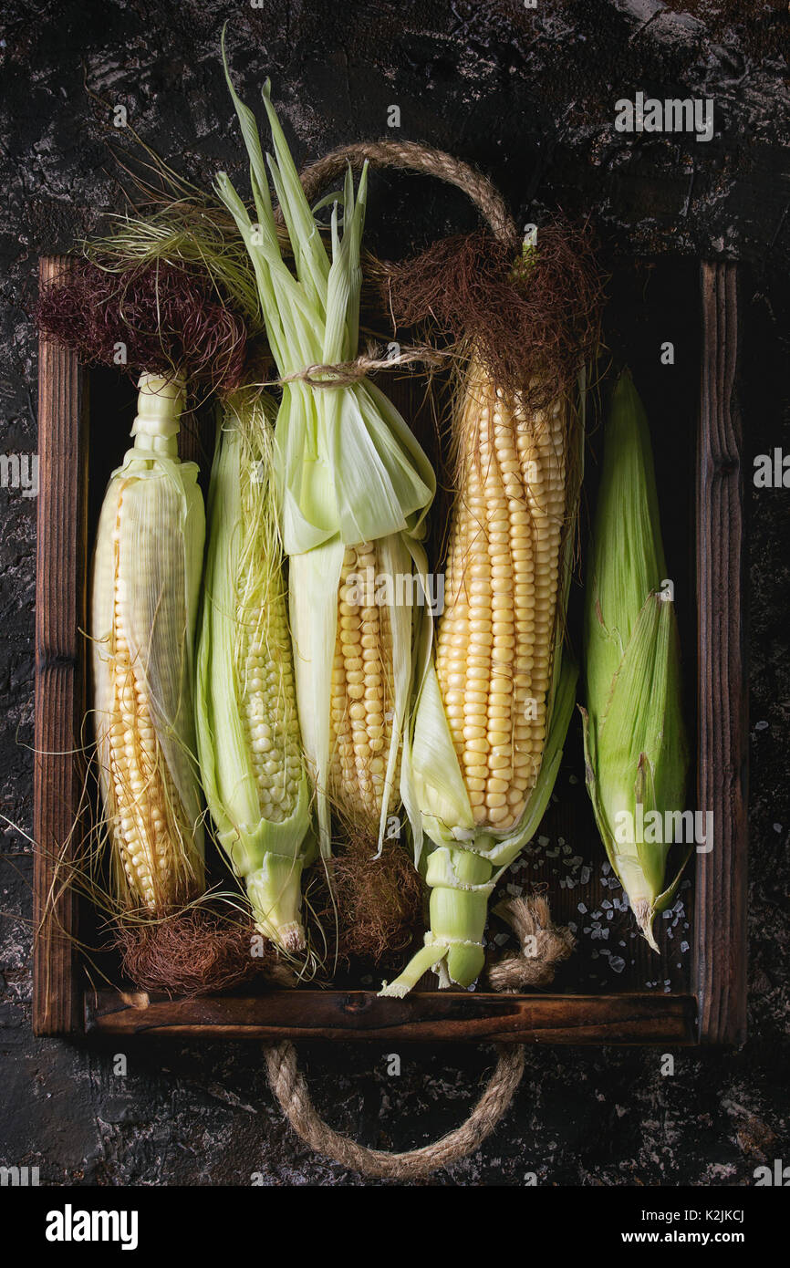 Young raw uncooked corn cobs in leaves in wooden tray. Top view over dark brown concrete texture background. - Stock Image