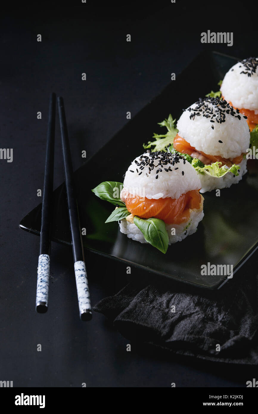 Mini rice sushi burgers with smoked salmon, green salad and sauces, black sesame served on black square plate with chopsticks and textile napkin over  - Stock Image