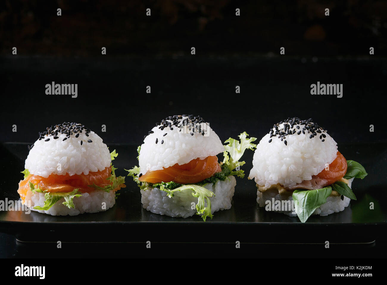 Mini rice sushi burgers with smoked salmon, green salad and sauces, black sesame served on black square plate with textile napkin over black backgroun - Stock Image