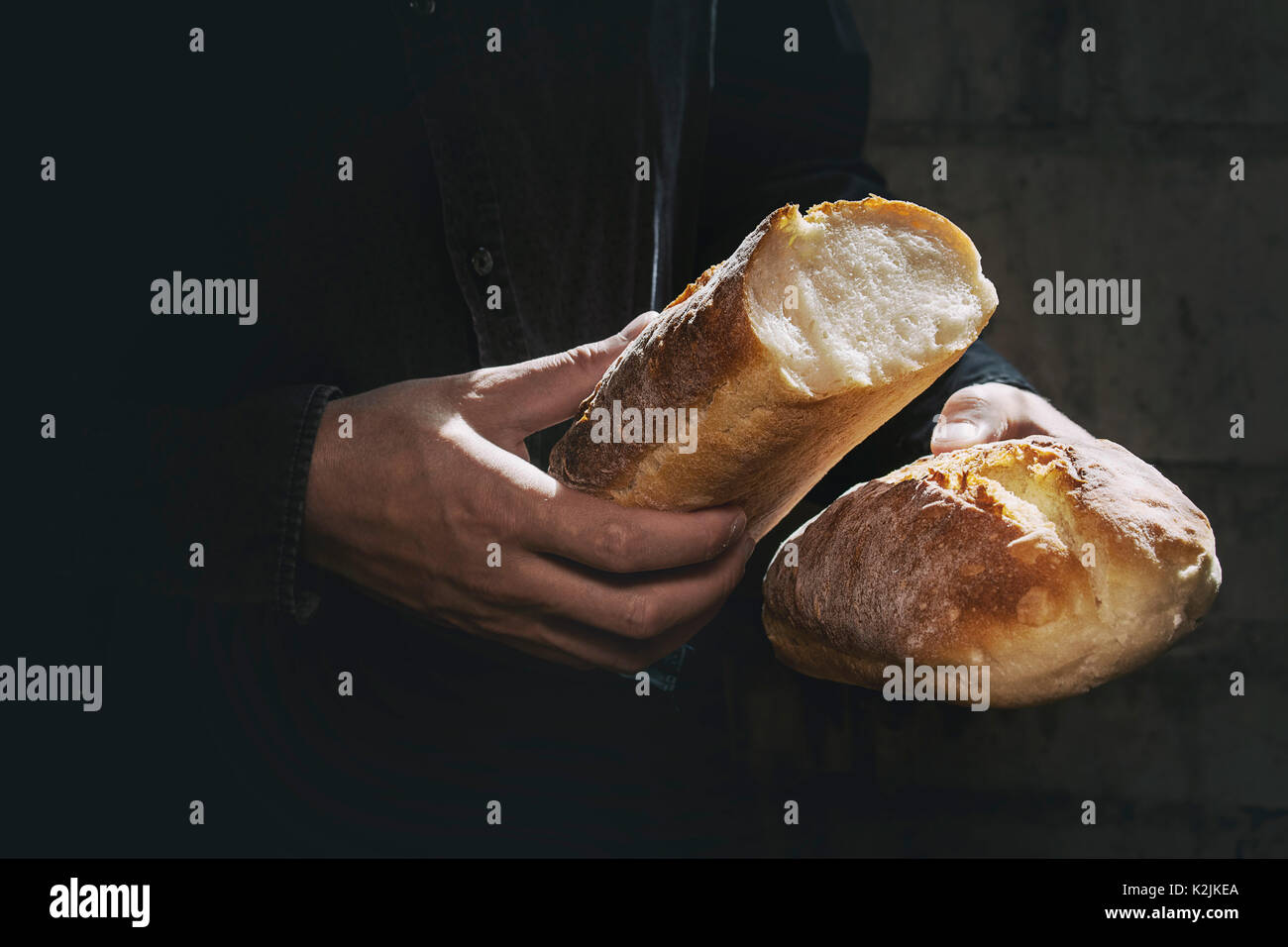 Loaf of fresh baked wheat bread in man's hands in sunshine. Rustic day light in dark room. Toned image - Stock Image