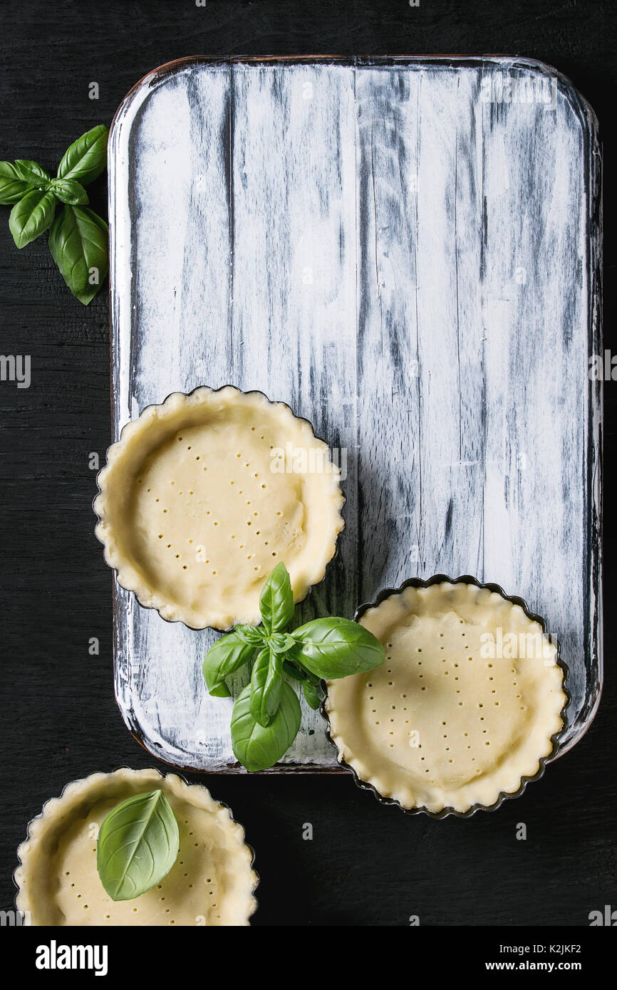 Dough for baking quiche tart in small baking form ready for bake with fresh basil on white wood serving board over black burned wooden background. Fla - Stock Image