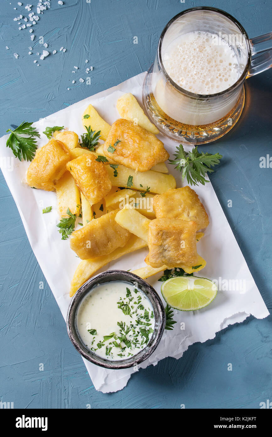 Traditional british fast food fish and chips. Served with white cheese sauce, lime, parsley, glass of lager beer on white paper over blue concrete bac - Stock Image