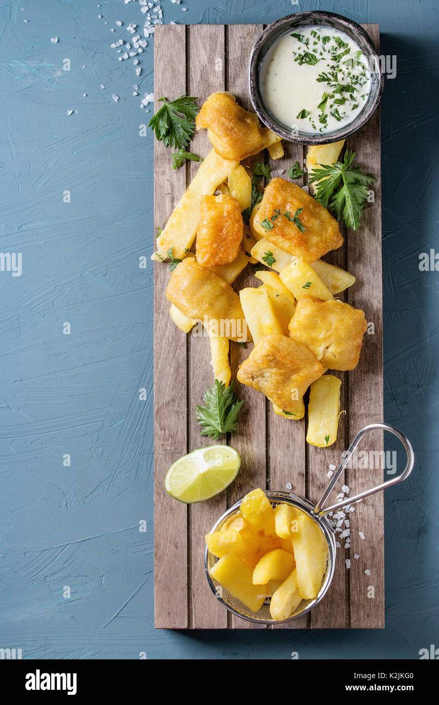 Traditional british fast food fish and chips. Served with white cheese sauce, lime, parsley, french fries in frying basket on wooden serving board ove - Stock Image