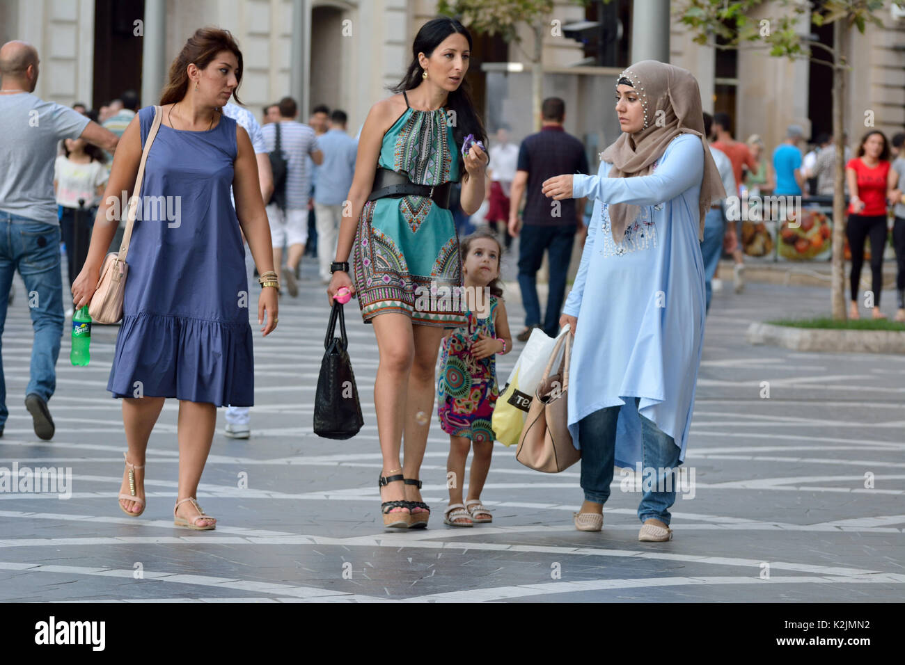 Woman wearing hijab and a woman in miniskirt with kid on the Fountains Square in Baku. - Stock Image