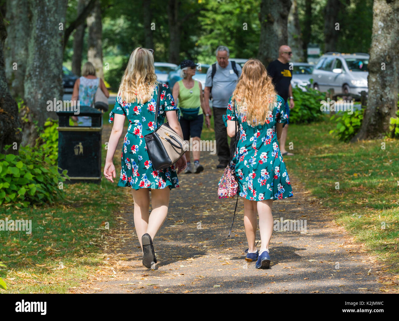 Pair of young women dressed in identical Summer dresses walking in Summer. 2 of a kind concept. Twins. Note: The women may or may not be related. - Stock Image