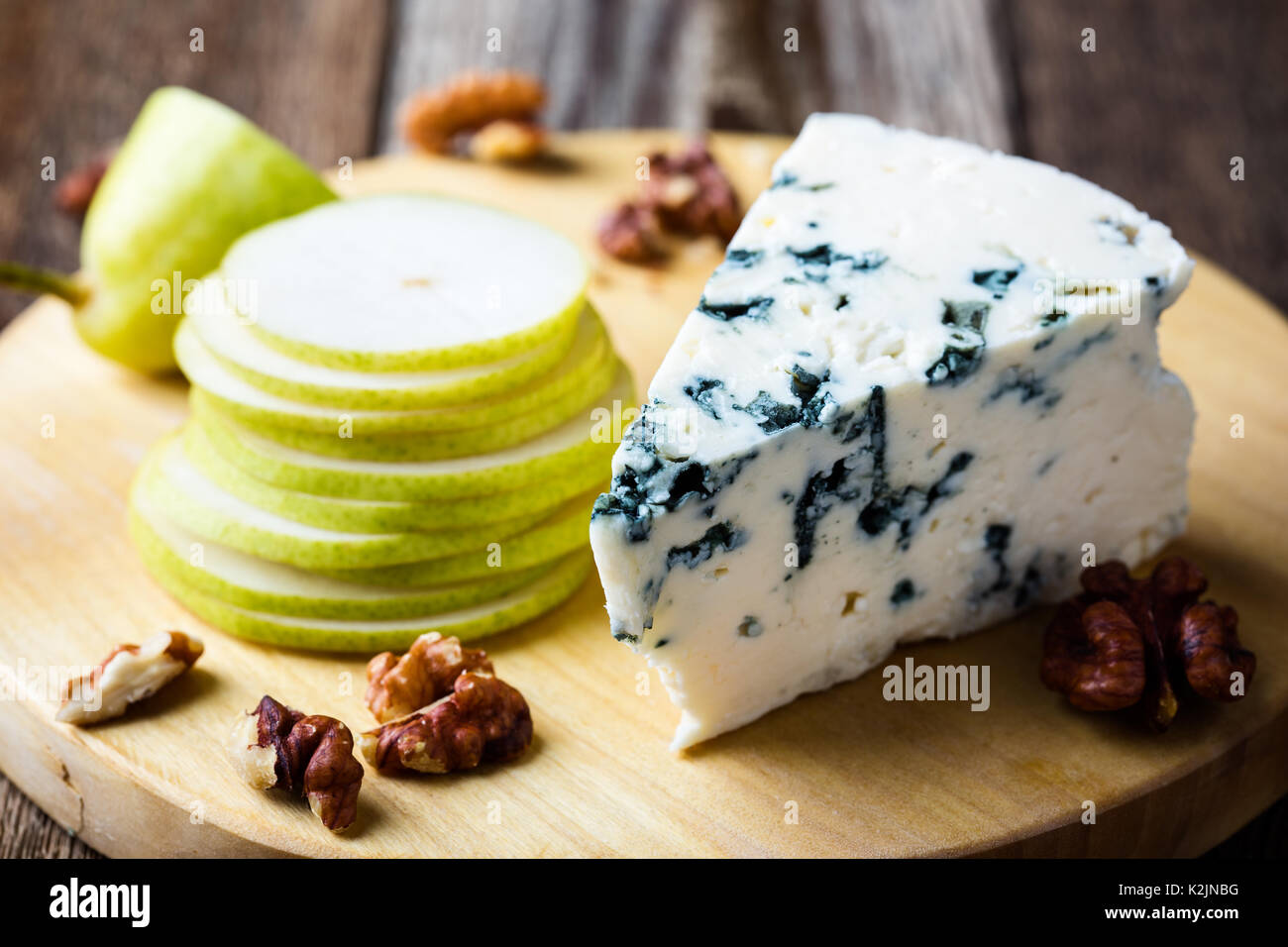 Cheese platter. Blue cheese  with fresh pear on rustic wooden board - Stock Image