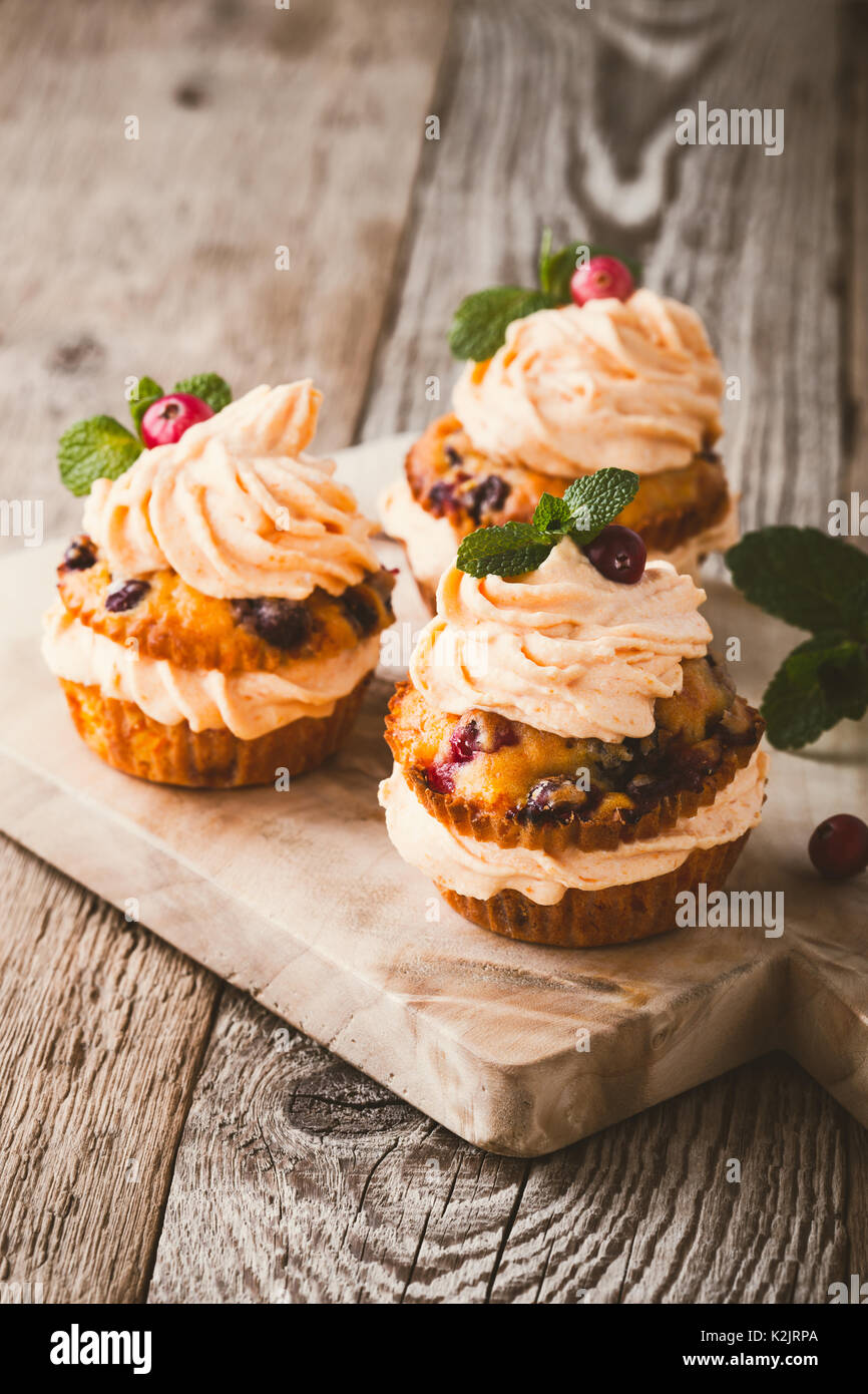 Cranberry pumpkin cupcakes with cream cheese frosting on rustic holiday table - Stock Image