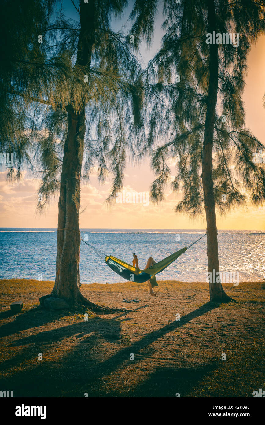 Silhouette of woman reading tablet in hammock,used split toning effect,vertical photo. - Stock Image