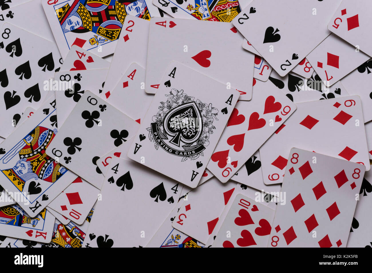 a deck of cards in a messy pile showing the Ace of Spades on top of the pile. - Stock Image