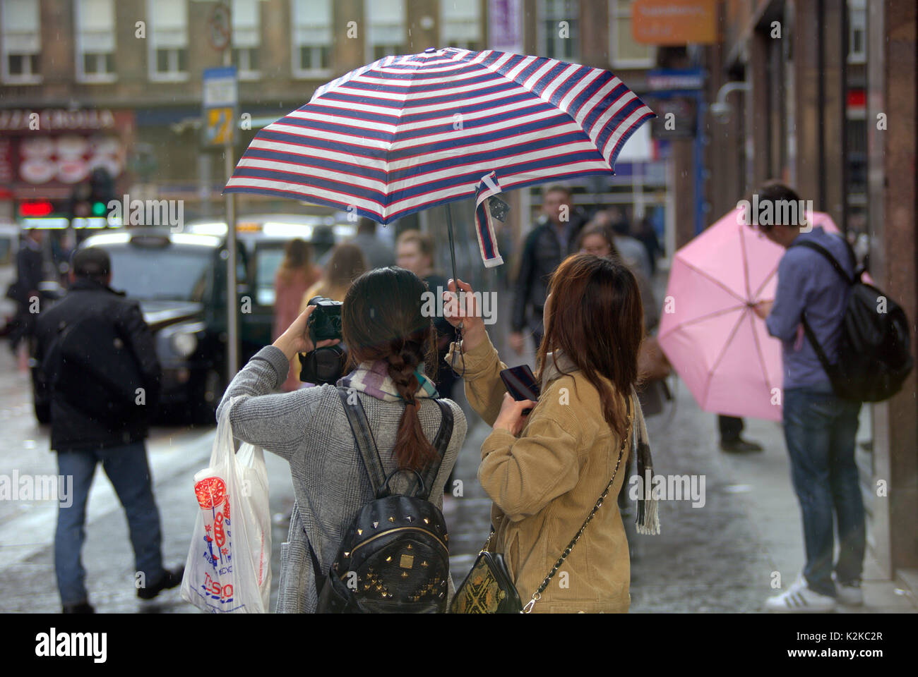 Glasgow, Scotland, UK. 30th Aug, 2017. UK Weather. Raining and sunny on the streets of the city often at the same tine as its poor summer weather continues. tourists marvel and take pictures of Sleet in summer outside central station. Credit: gerard ferry/Alamy Live News - Stock Image
