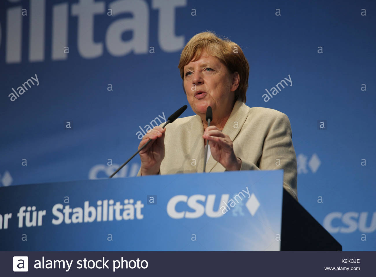 Angela Merkel lowers the microphones as she begins to speak to a large crowd in Erlangen, Bavaria. She is on the campaign trail in the run up to the German election which is taking place on Sunday, September 24.Merkel spoke for over forty minutes and was well received though a small group of protestors tried to interrupt her speech with whistles and catcalls. - Stock Image