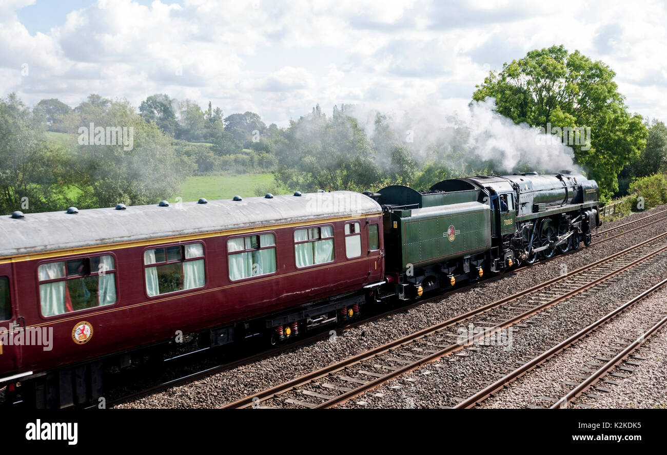 Hatton, Warwickshire, UK. 31st Aug, 2017. UK. Britannia class steam locomotive 'Oliver Cromwell' along with a support coach descends Hatton Bank in the Warwickshire countryside. The preserved locomotive was travelling between the Tyseley Steam Trust in Birmingham and the Great Western Society railway museum at Didcot, Oxfordshire. Credit: Colin Underhill/Alamy Live News - Stock Image