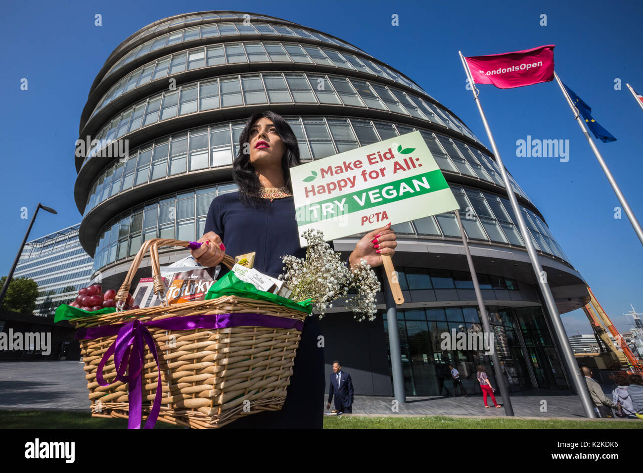 London, UK. 31st August, 2017. PETA protest outside City Hall. Asifa Lahore, Britain's first out Muslim drag queen, poses for photos with a hamper of vegan goodies from PETA before delivering them to London Mayor Sadiq Khan's office for Eid al-Adha holy celebration. Credit: Guy Corbishley/Alamy Live News - Stock Image