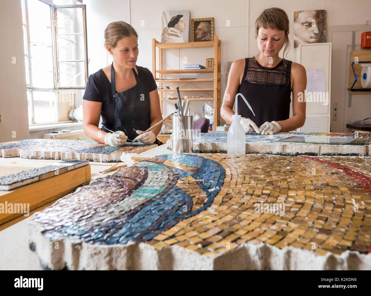 Erfurt, Germany. 31st Aug, 2017. Janka Acht (l) and Simone Schmiedkunz restore fragments of the monumental St. Mary's mosaic which will be displayed in the roof truss of the dome in Erfurt, Germany, 31 August 2017. The artwork used to hang on the western facade of the dome, but had to be taken down during deconstruction works on the roof of the long house ('Langhaus') in 1968. The mosaic has not been displayed publically ever since. Photo: Arifoto Ug/Michael Reichel/dpa-Zentralbild/dpa/Alamy Live News - Stock Image