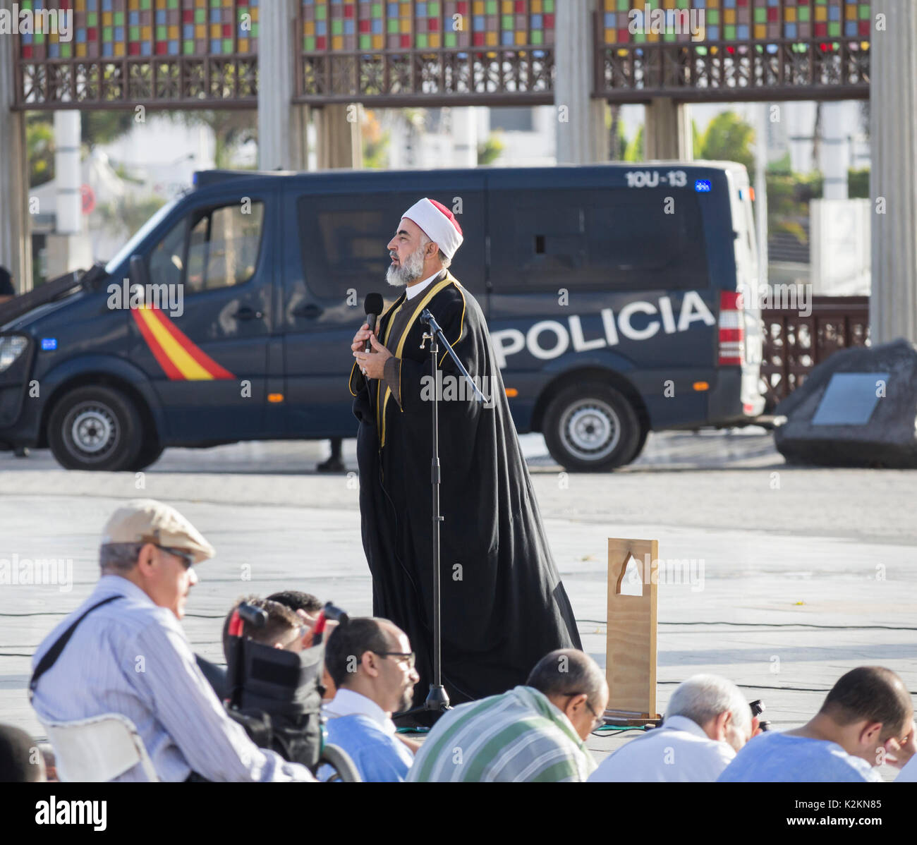 Las Palmas, Gran Canaria, Canary Islands, Spain. 1st September, 2017. Spain: Hundred of Muslims in Las Palmas, the capital of Gran Canaria, gather for prayers to celebrate Eid al-Adha ( 'sacrifice feast') on Friday morning. PICTURED: An Iman speaks to hundreds gathers for Eid al-Adha prayers with Spanish police in close proximity. - Stock Image