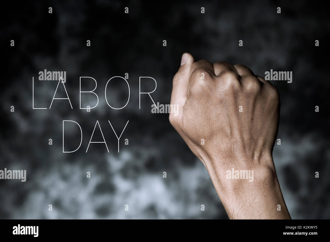 closeup of the raised fist of a young man against a gradient dark gray background and the text labor day - Stock Image