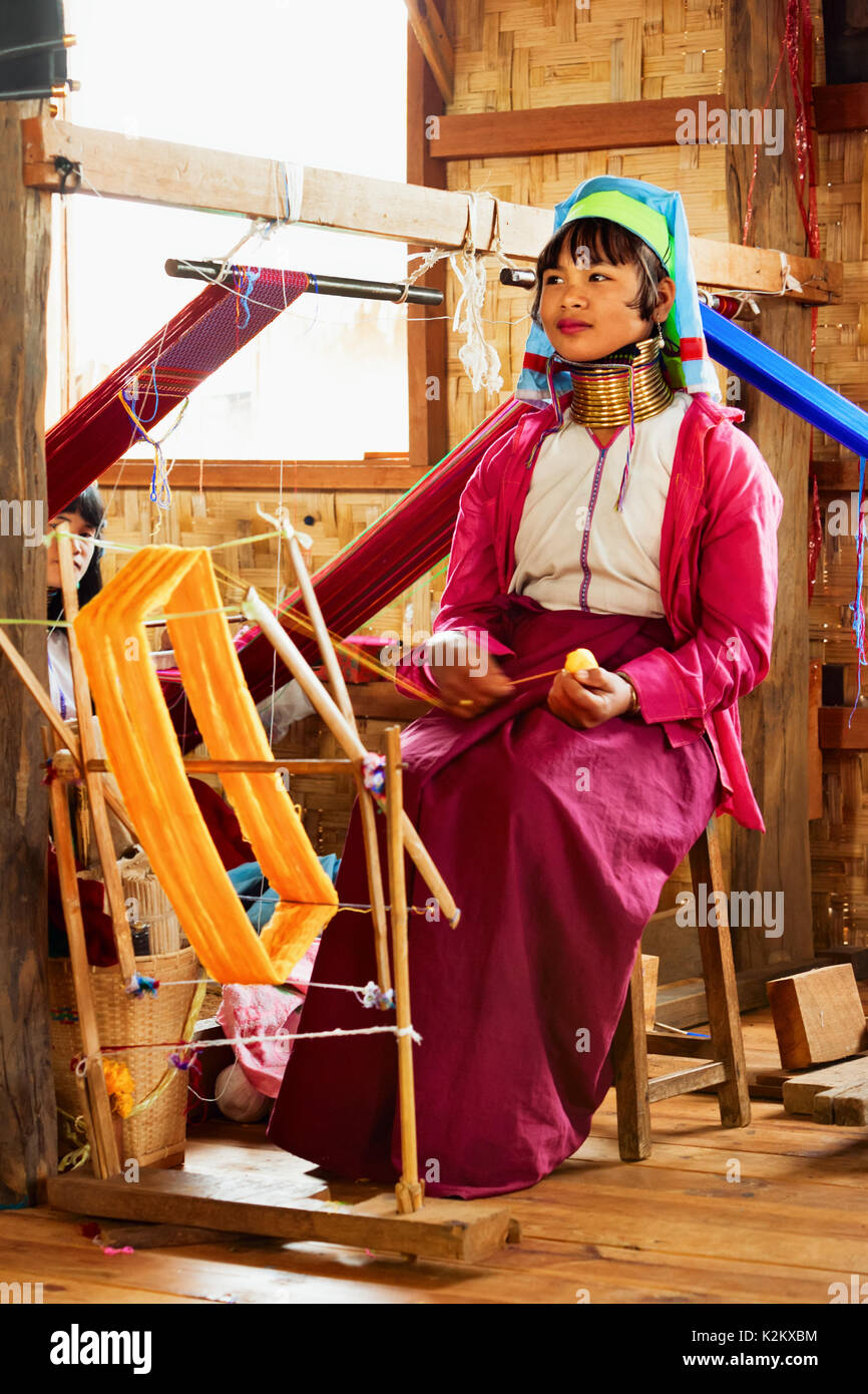Inle Lake, Myanmar - January 04, 2007: Young woman of Kayan Lahwi (Padaung) people wearing brass coils on long neck weaving traditional textile Stock Photo