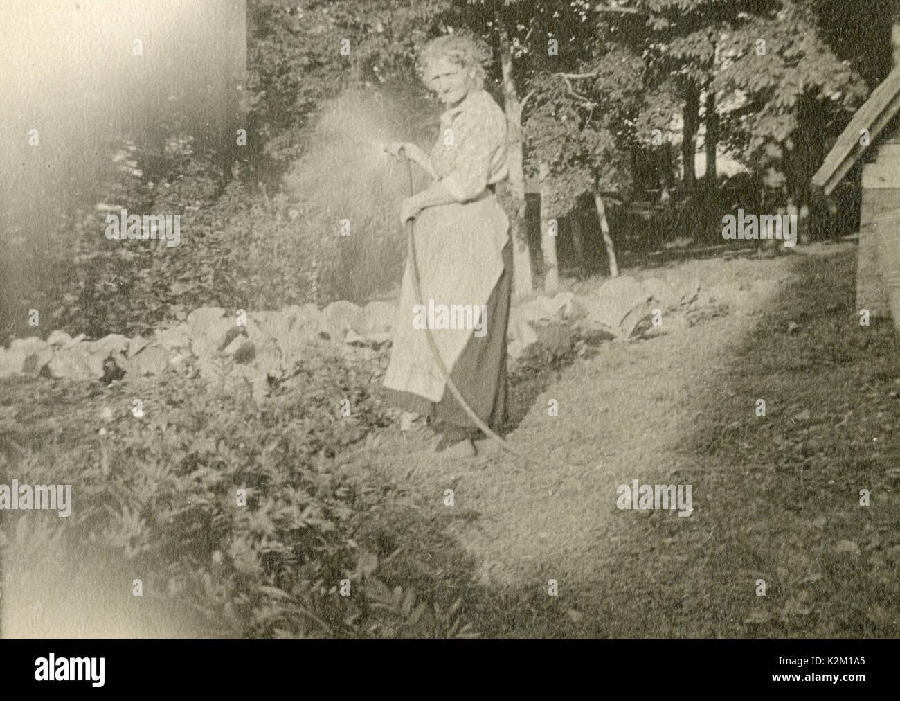 Antique c1930 photograph, elderly woman watering her garden. SOURCE: ORIGINAL PHOTOGRAPH. - Stock Image