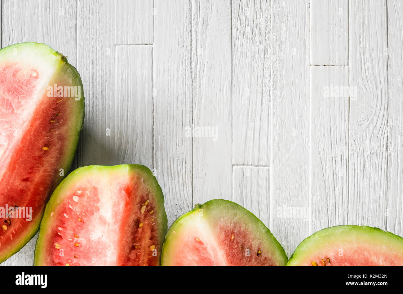 Watermelon slices on a light rustic wooden background top view. Copy space background with empty blank space for text - Stock Image