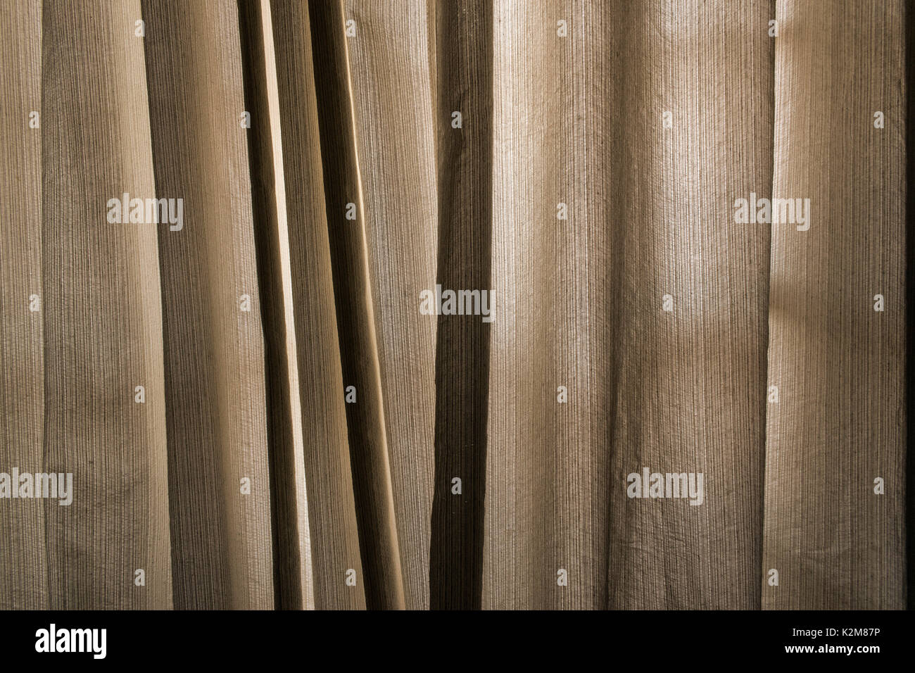 Yellow and beige window drapes, with difused backlit, texture and pattern - Stock Image