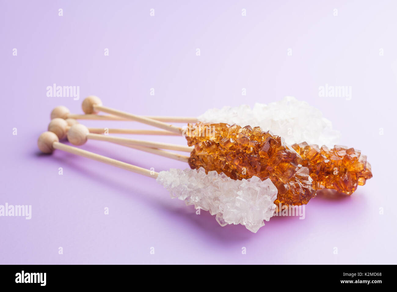 Crystalline sugar on wooden stick. Brown and white sugar. Refined and unrefined sugar. - Stock Image