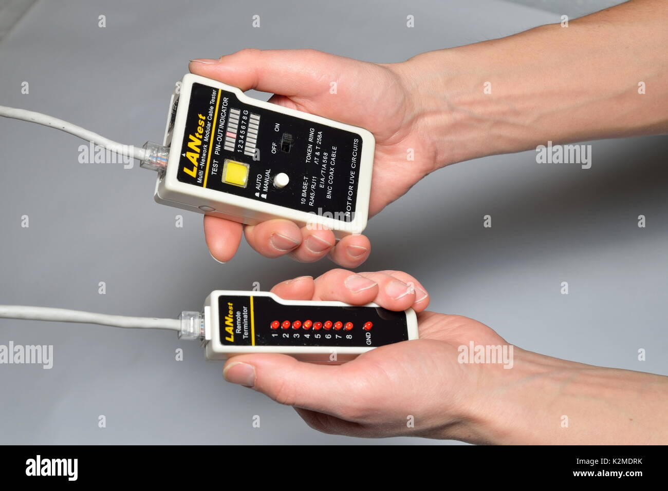 Hand of the master LAN check tester for crimped wire local area  Stock Photo