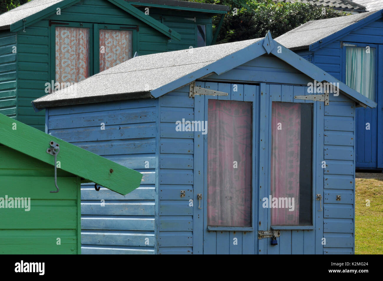 Brightly coloured beach huts on the seashore in a coastal scene on the beach Isle of Wight holida homes and chalets Stock Photo