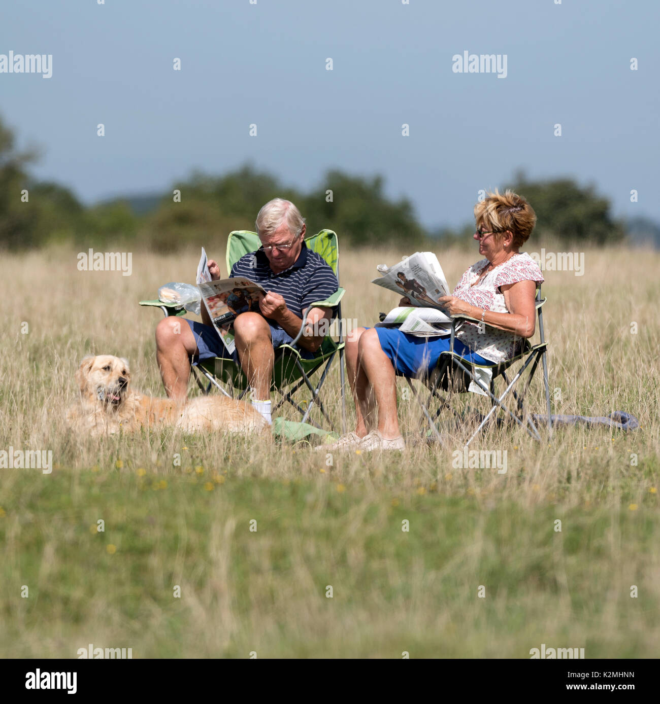 Elderly couple with a dog relax reading newspapers in the late summer sunshine in the Cotswolds region of England UK. August 2017 - Stock Image