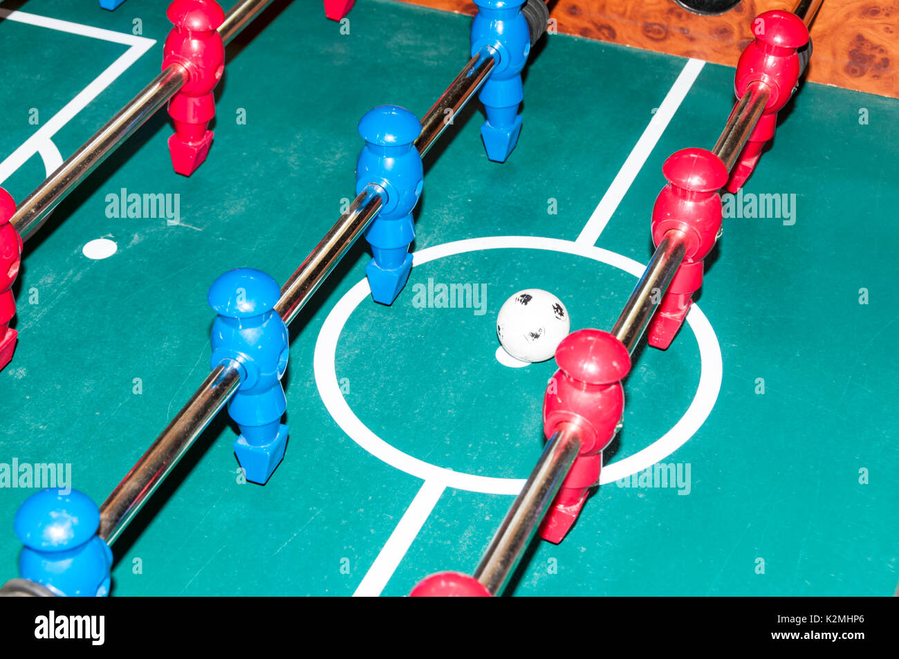 Red and blue teams lined up for the kick-off in a game of table football - Stock Image