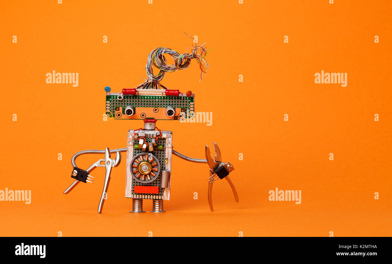 Funny robot electrician with pliers. Creative design robotic toy with electric wires hairstyle, electronic circuits, chip capacitors vintage resistors. Orange background copy text - Stock Image