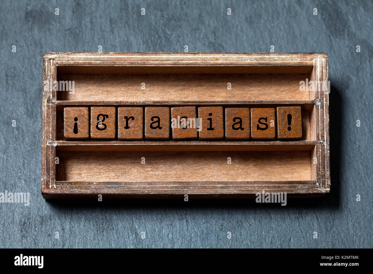 Gracias. Thank you in Spanish translation. Vintage box, wooden cubes phrase with old style letters. Gray stone textured background. Close-up, up view, soft focus. - Stock Image
