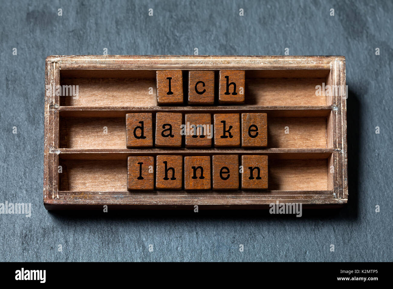 Ich danke Ihnen. Thank you in German translation. Vintage box, wooden cubes thankful phrase message written with Stock Photo