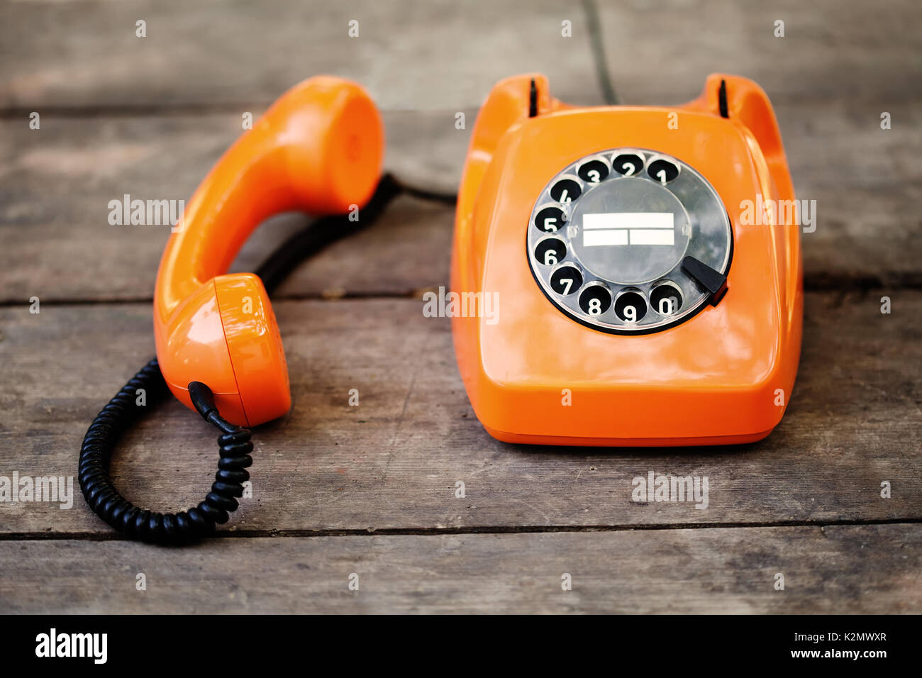 Busy retro phone orange color, handset receiver on wooden textured background. Shallow depth field photography - Stock Image